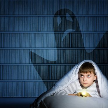 image of a boy under the covers with a flashlight the night afraid of ghosts